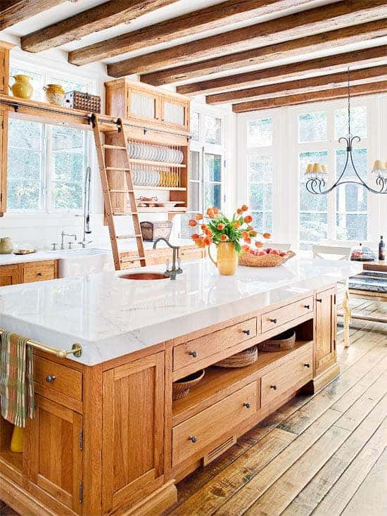 Gorgeous kitchen with wooden beams, open upper natural wood cabinets, and lower natural wood cabinets. Kitchen island with thick marble slab.