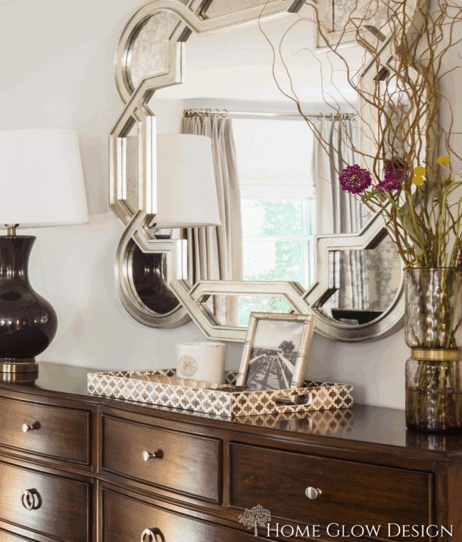 serene master suite makeover reveal bedroom champagne mirror dresser vignette purple lamp