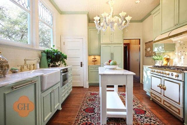 Super cute mint green kitchen with a long narrow island in the middle.